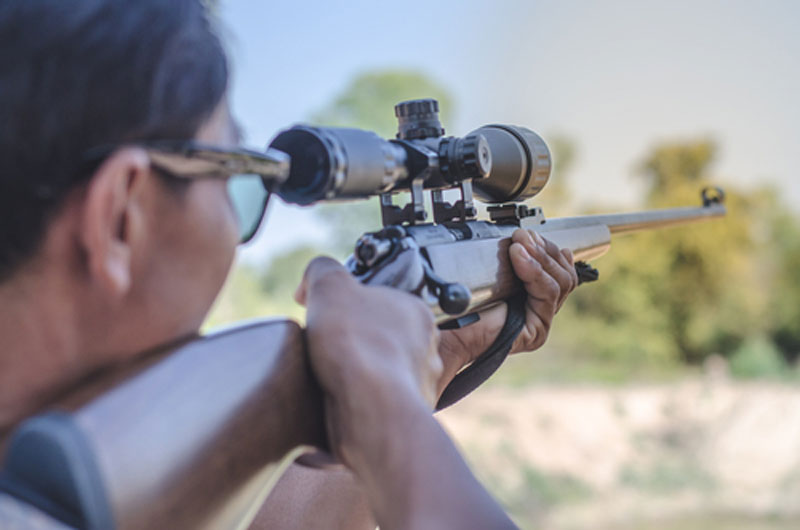 Man taking aim through rifle scope while target shooting