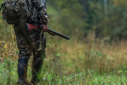 Man in camo standing with rifle near woods