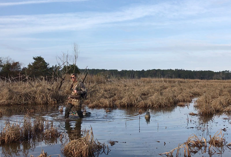 Woman in camo walking through swamp looking to pickup a decoy