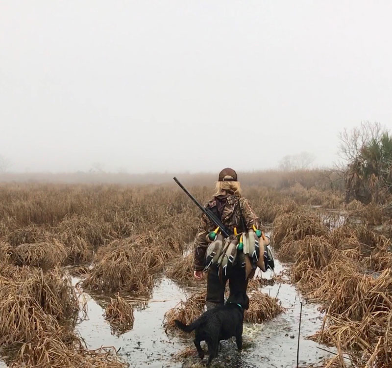 Woman with dog walking through field on duck hunt