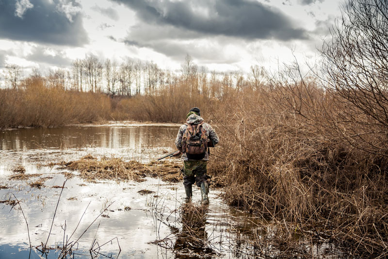 The Ultimate Packing Guide for Your Next Hunting Trip 4 - hunter wading through swamp