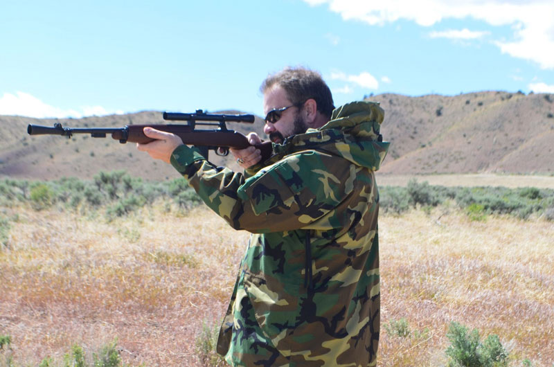 Author in camo jacket taking aim with a top hunting rifle