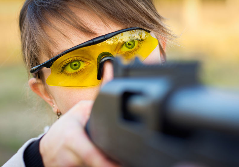 A young girl with a gun for trap shooting and shooting glasses aiming at a target