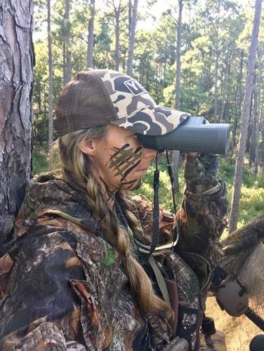 Woman in camo looking through binoculars