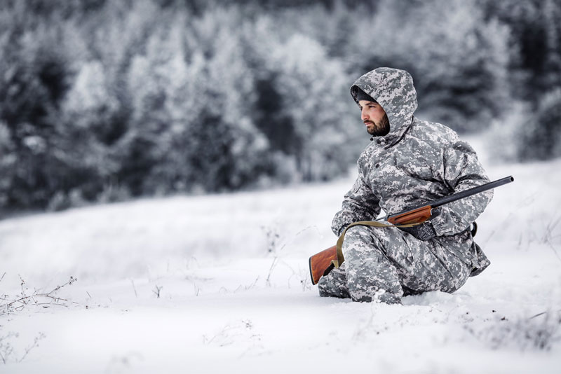 Hunter crouched in white camo attire in winter