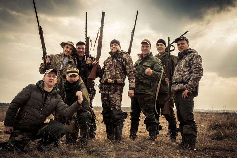 Group of eight hunters standing together against sunrise sky in rural field during hunting season