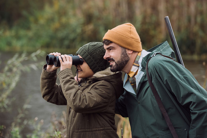 Father and son hunting while son looks through binoculars